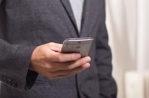 Checkliste Geschäftsreise Anzug und Smartphone